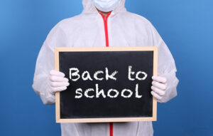 Picture of a person in protective colthing with a back to school sign
