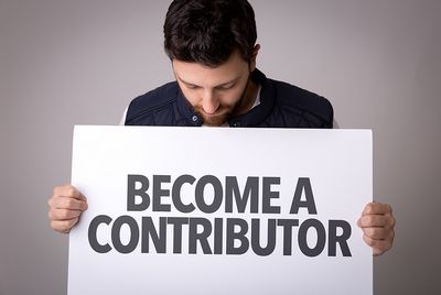 Yound man holding a placard with the text Become a Contributor